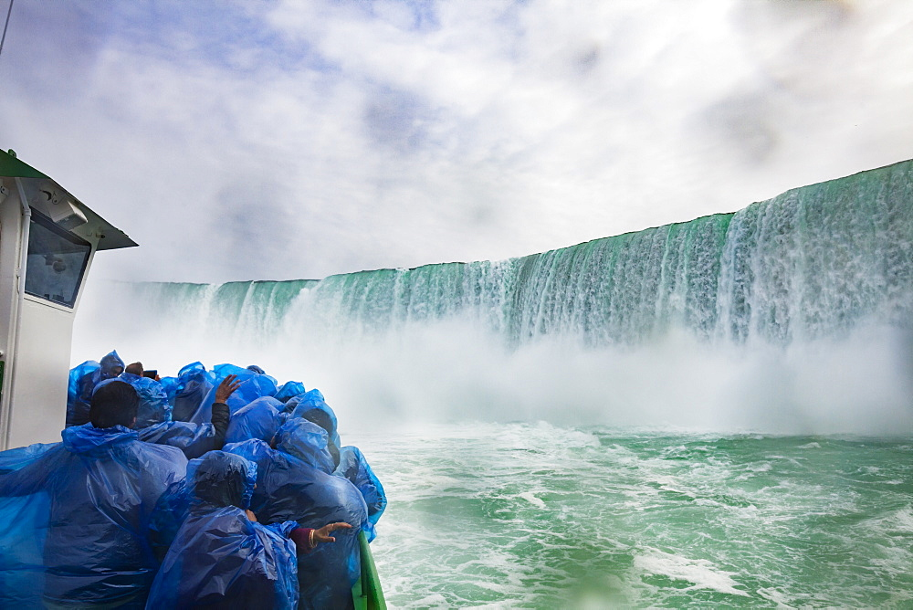 A boat of tourists huddle under blue plastic ponchos to keep the drenching waterfall spray off as the boat, ?Maid of the Mist? brings them to the base of Niagara Falls, on the Niagara River.