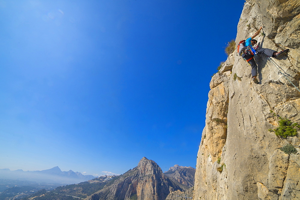 A man lead climbing a technical rock route in Costa Blanca Spain at Sierra de Toix.