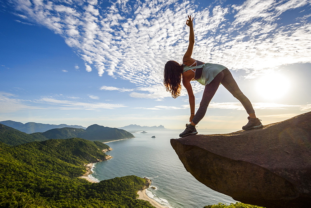 Woman in yoga posture on the edge of the mountain in Pedra do Telégrafo, Barra de Guaratiba, west side of Rio de Janeiro, Brazil