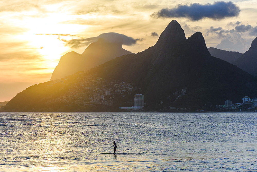 Local riding a stand up paddle board during sunset in Ipanema Beach, Morro Dois Irmaos on the back, Rio de Janeiro, Brazil