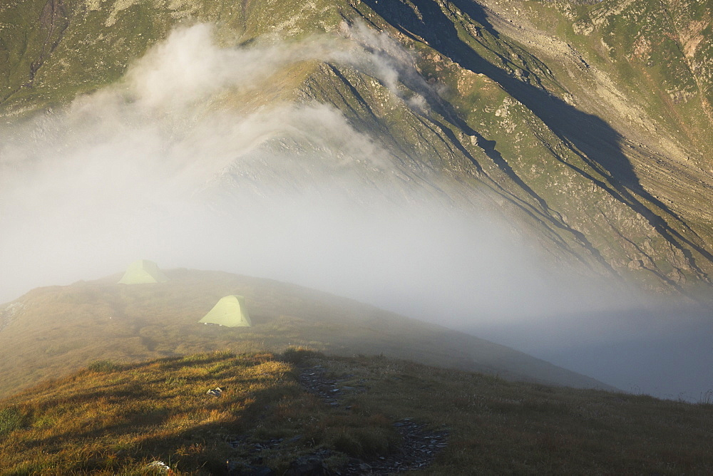 Tents in alpine environment engulfed by fog at sunrise