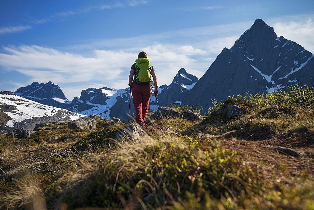 Female hiker hiking trail towards Flakstadtind mountain peak, Flakstadøy, Lofoten Islands, Norway