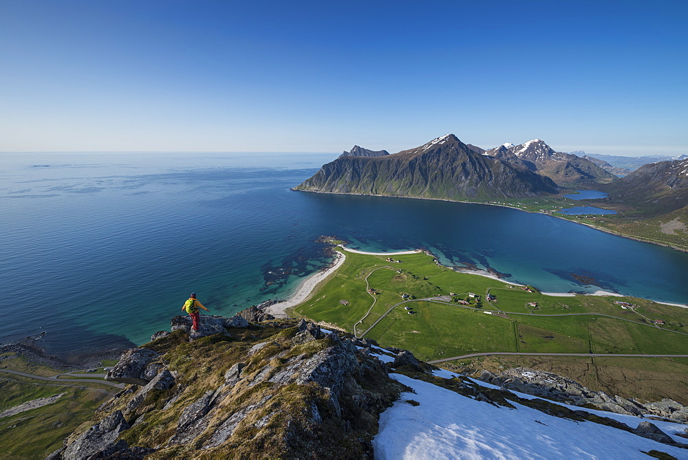 Female hiker enjoys view of beaches and coast from summit of Flakstadtind mountain peak, Flakstadøy, Lofoten Islands, Norway