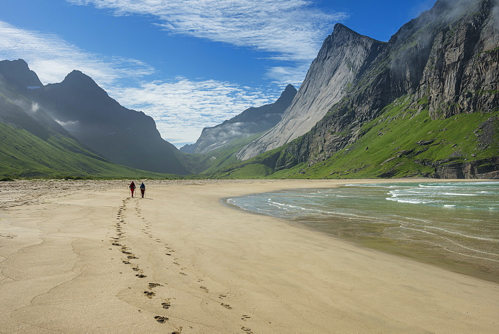 Two hikers leave footprints in sand at Horseid beach, Moskenesøy, Lofoten Islands, Norway