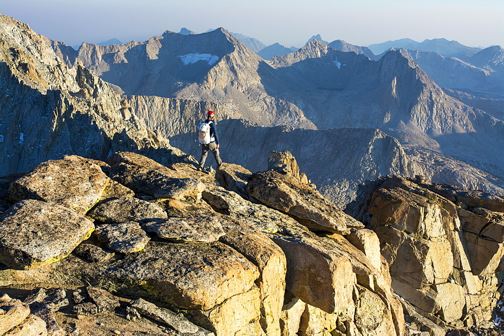 A man hiking along the summit of Mount Mendel along the 8.5 mile Evolution Traverse, John Muir Wilderness, Kings Canyon National Park, Bishop, California.