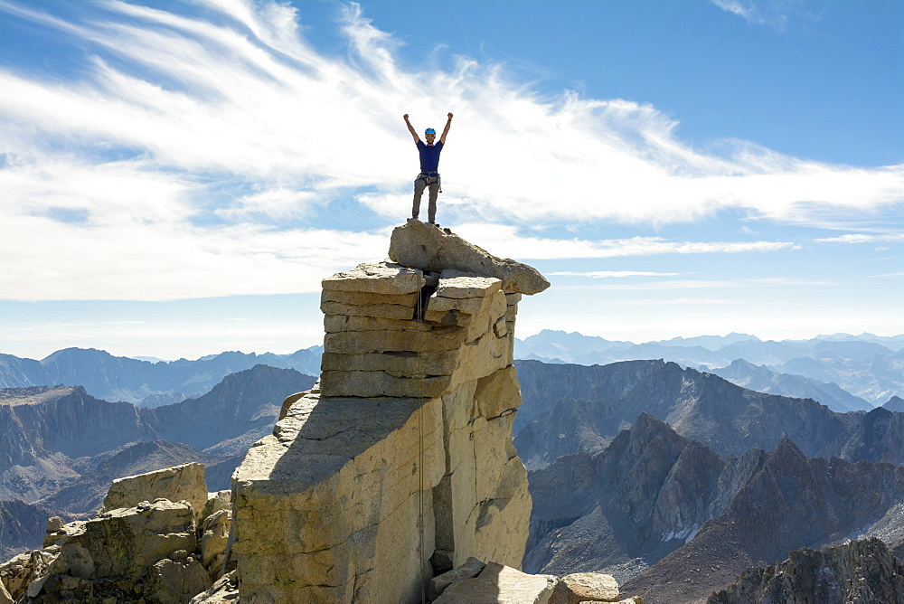 A man standing on the Mount Darwin summit along the 8.5 mile Evolution Traverse, John Muir Wilderness, Kings Canyon National Park, Bishop, California.