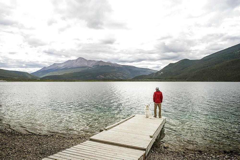 Muncho Lake British Columbia man and dog on dock