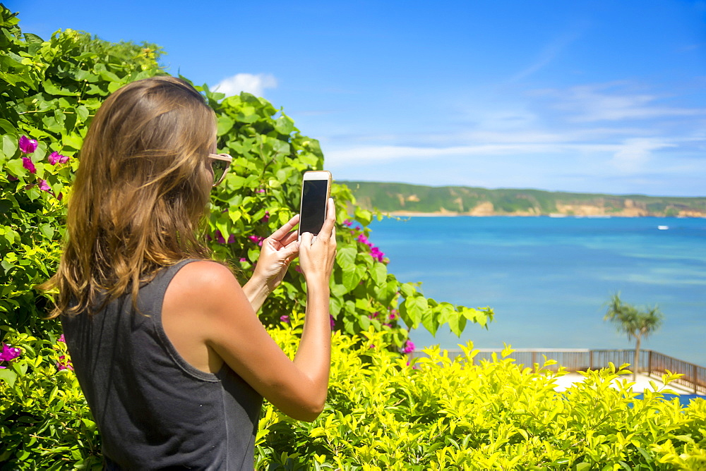 Female tourist taking picture with smart phone