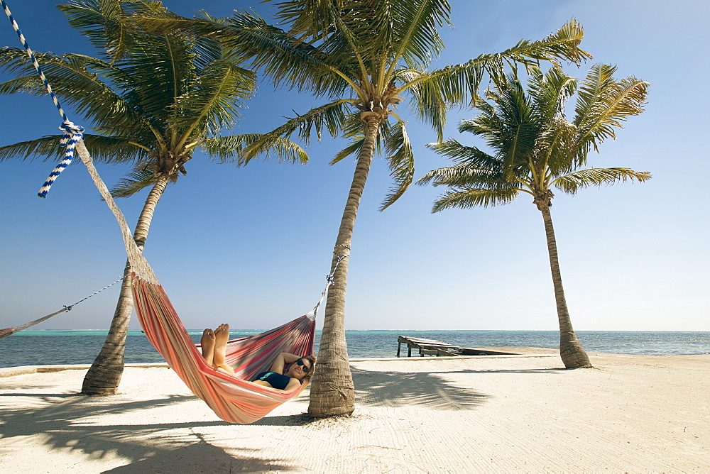 A Young Woman relaxes in a hammock on the beach with a view of the ocean horizon