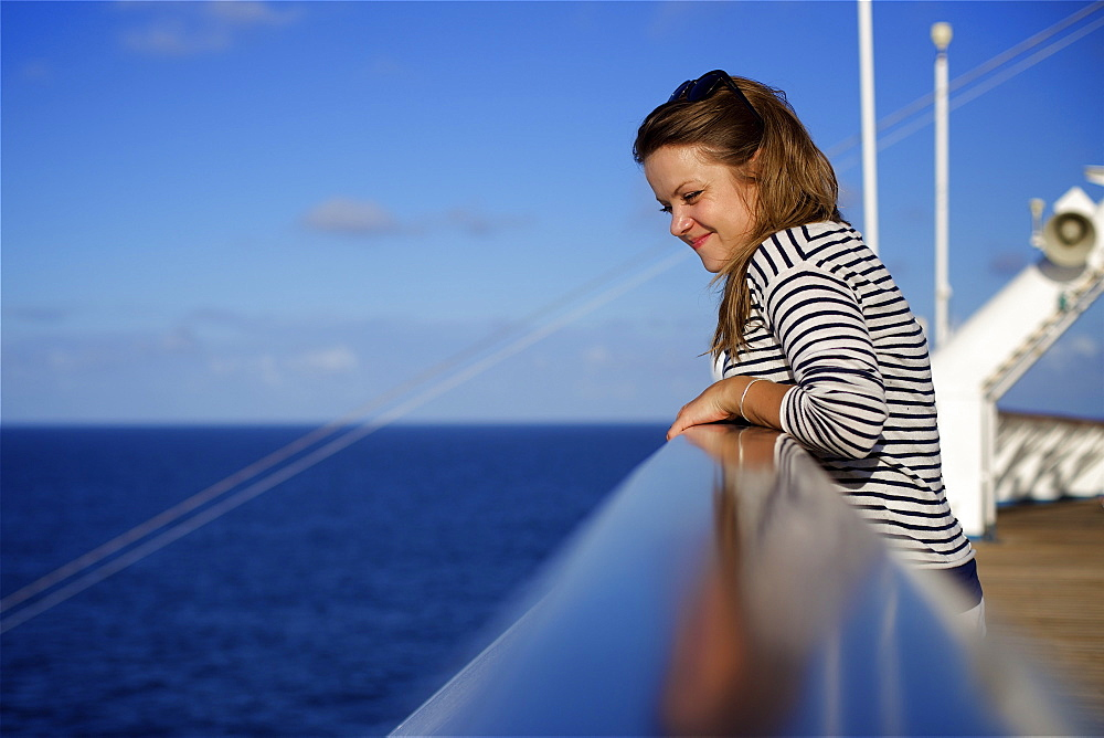 A young woman leans over the railing on the deck of a cruise ship