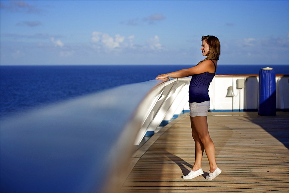 A young woman looks over the railing on the deck of a cruise ship