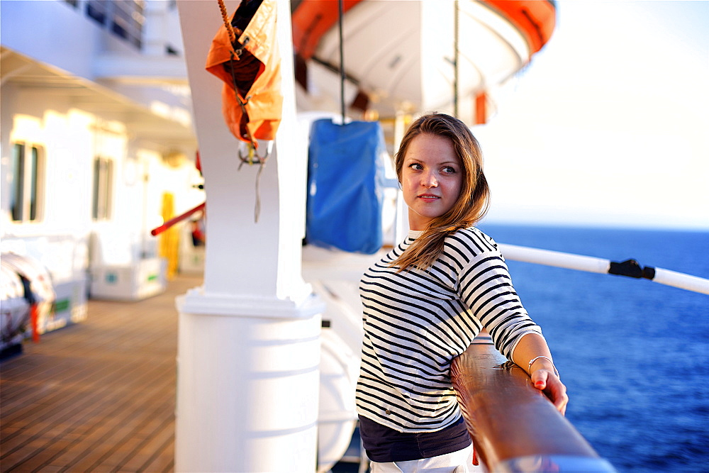 A young woman leans against the railing on the deck of a cruise ship