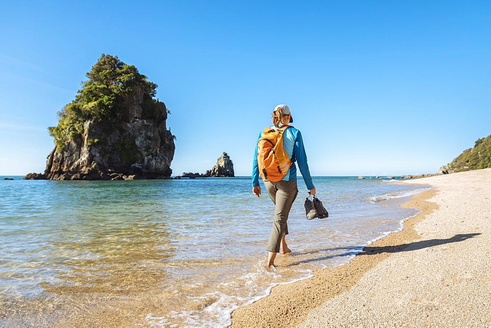A woman is walking on a beach in Abel Tasman National Park