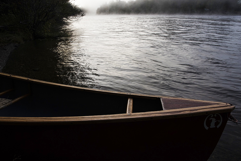 A canoe along teh side of a river in Maine.