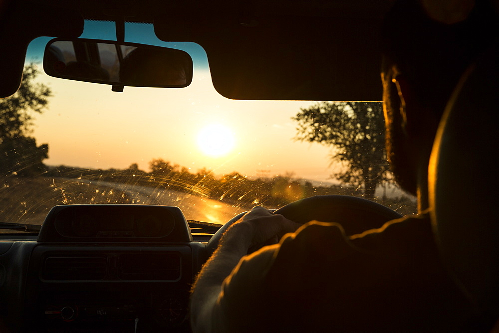 A male drives his truck towards the sunset in Zimbabwe