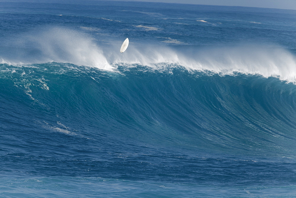 A surfer wiping out on a huge wave at Waimea Bay.