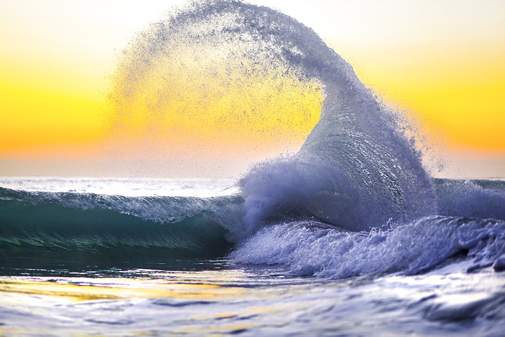 A collision of waves captured againnst a lemon yellow sunrise in Hawaii.