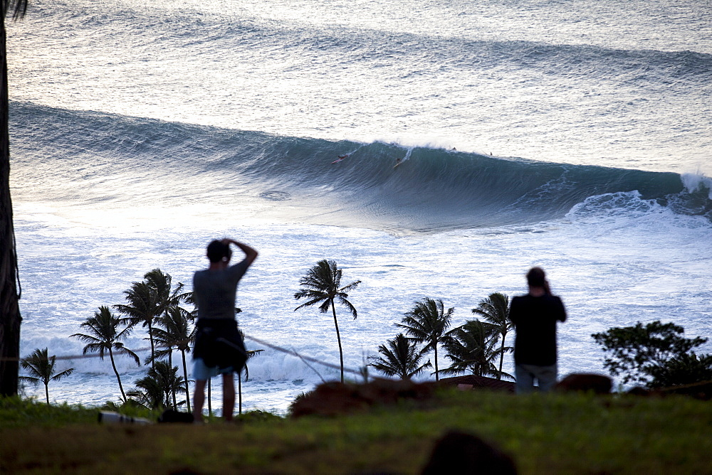 Spectators watching big surf at Waimea Bay, on the north shore of Oahu.