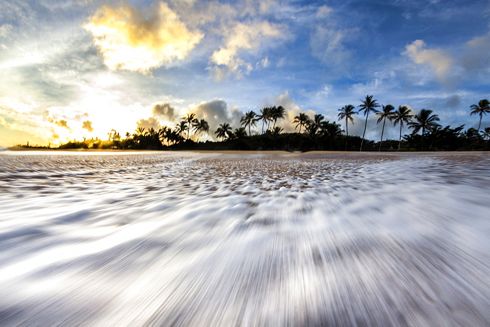 A time lapse of a wave rushing back down the beach on the north shore of oahu, during sunrise.