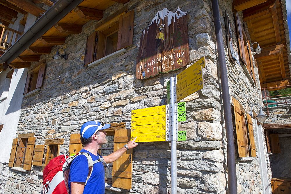 A hiker is looking at a sign post near Courmayeur, half way the Tour du Mont Blanc, a classic multi day hike around the highest mountain of the European Alps. The trek takes about 10 days and goes through France, Italy and Switzerland.