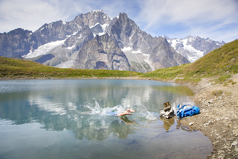 A male hiker is taking a bath in a mountain lake near Courmayeur in the Italian Alps, with Mont Blanc in the back ground. This is halfway the Tour du Mont Blanc, a classic trekking that goes through France, Italy and Switzerland.
