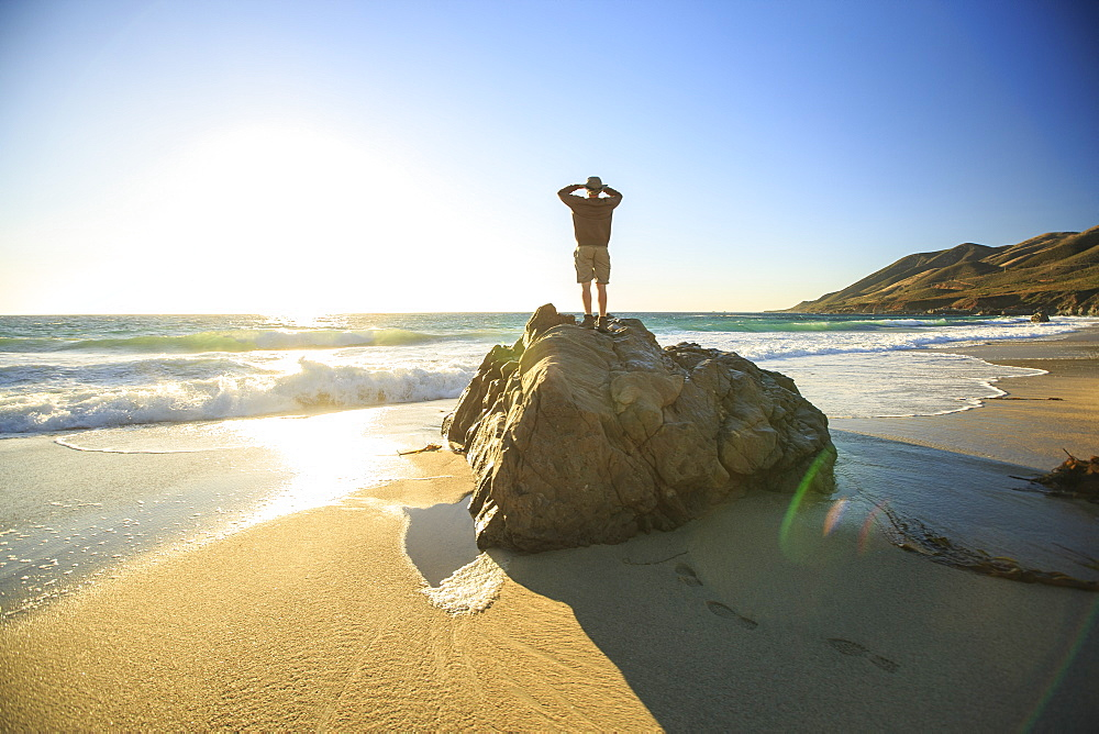 A man standing on a boulder at a beach looks out at the Pacific Ocean at sunset near Big Sur California.