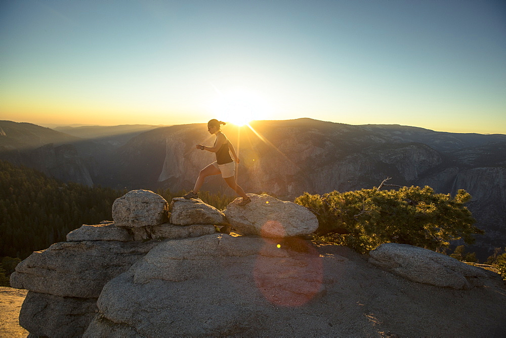 A hiker walks along rocks at Sentinel Dome in Yosemite National Park at sunset.