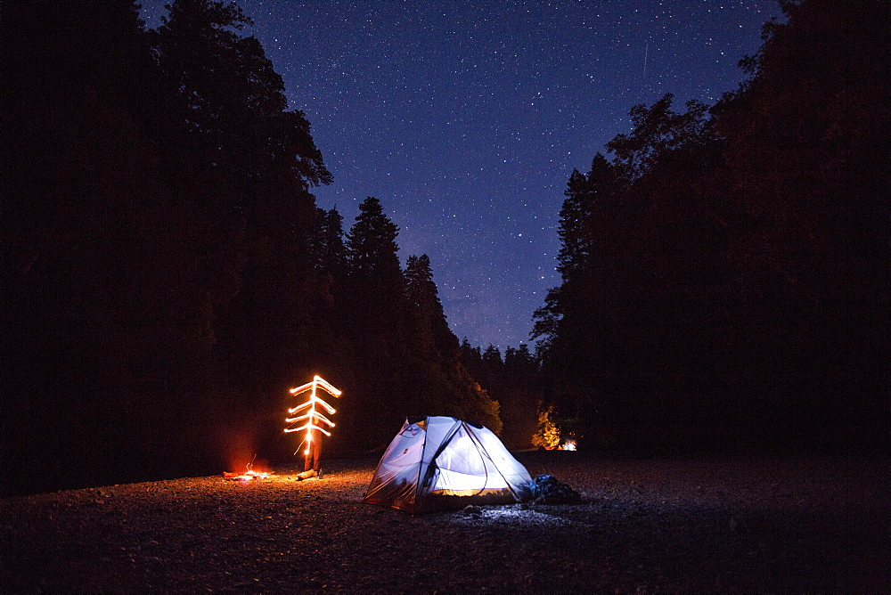 An illuminated tent sits next to a campfire on a river bed under a clear night sky with stars.