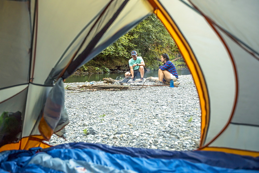 Two hikers tend to a campfire next to their tent on a riverbed.