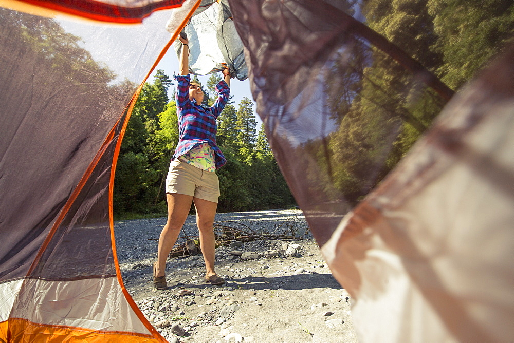 A female hiker opens her tent fly to set up camp on a riverbed in California.