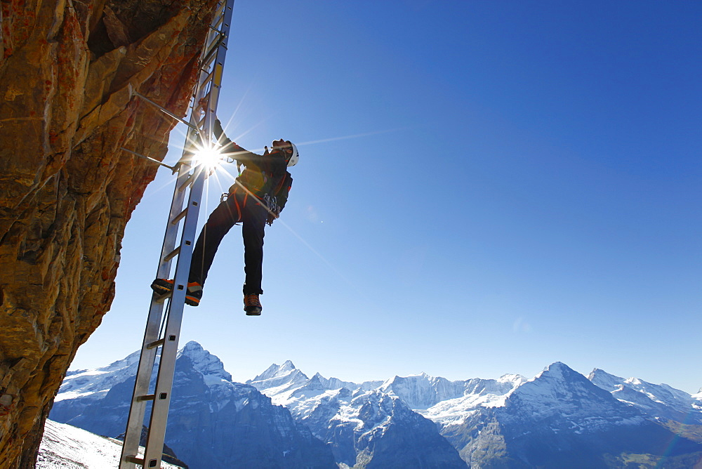 A climber on a ladder of the Klettersteig to the top of the Schwarzhorn, a mountain above Grindelwald in the Swiss Alps.
