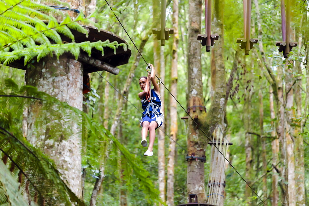 A girl descends a zipline at a Treetop Adventure Park, Bali, Indonesia - 857-94743