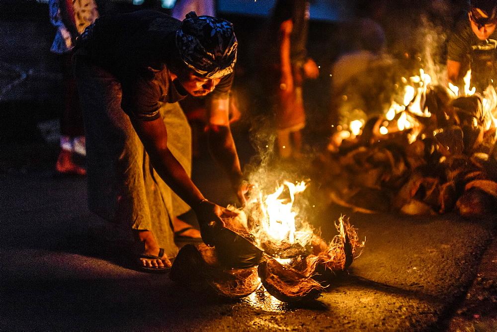 Person burning coconut husks at night, Tabanan, Bali, Indonesia