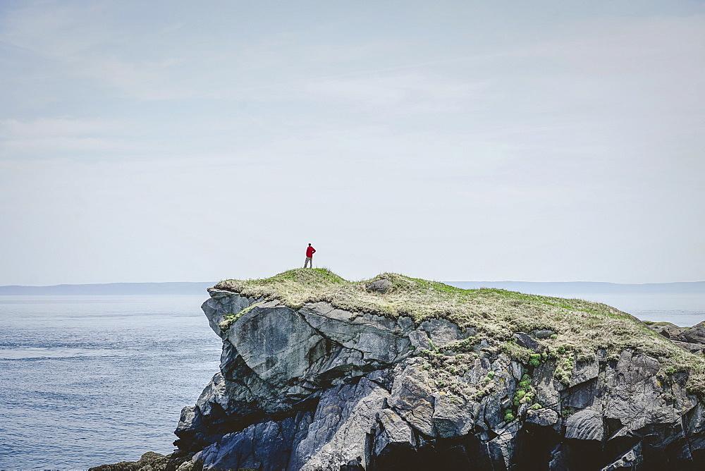 Man of cliff edge overlooking Bay of Fundy Atlantic Ocean from Campobello Island New Brunswick