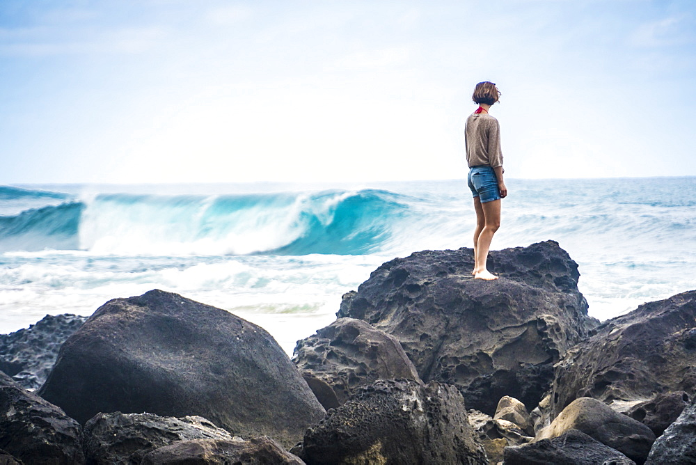 A woman stands on the rocks to look at the waves near Tunnels Beach, Kauai, Hawaii