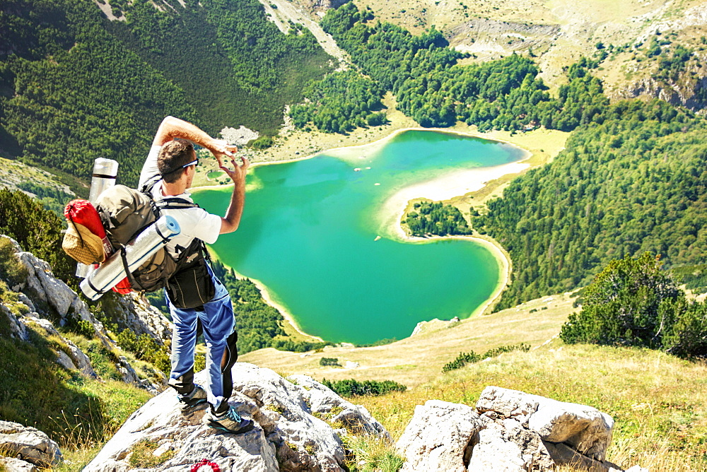 Hiker standing on the rock, high above heart shaped lake in Montenegro. Trnovacko lake on Bioc mountain.
