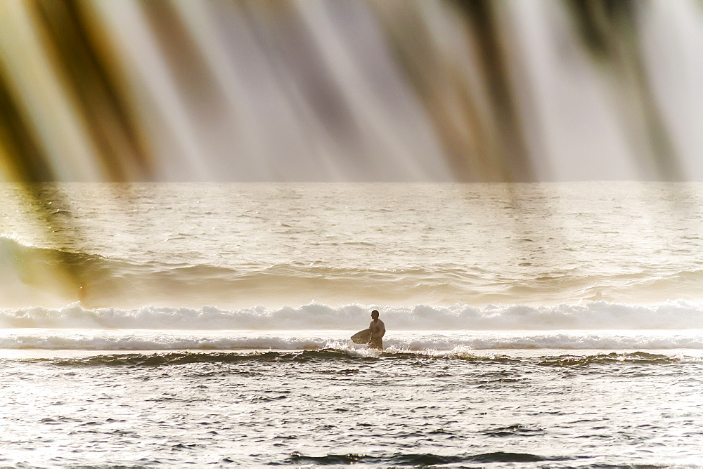 Surfer standing in sea with waves, Lakey Peak, central Sumbawa, Indonesia