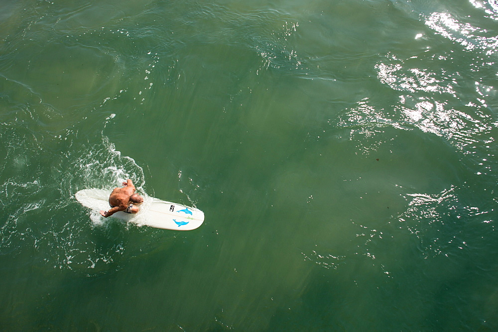 Senior man paddling surfboard next to pier near promenade on Golden Mile, Durban, South Africa