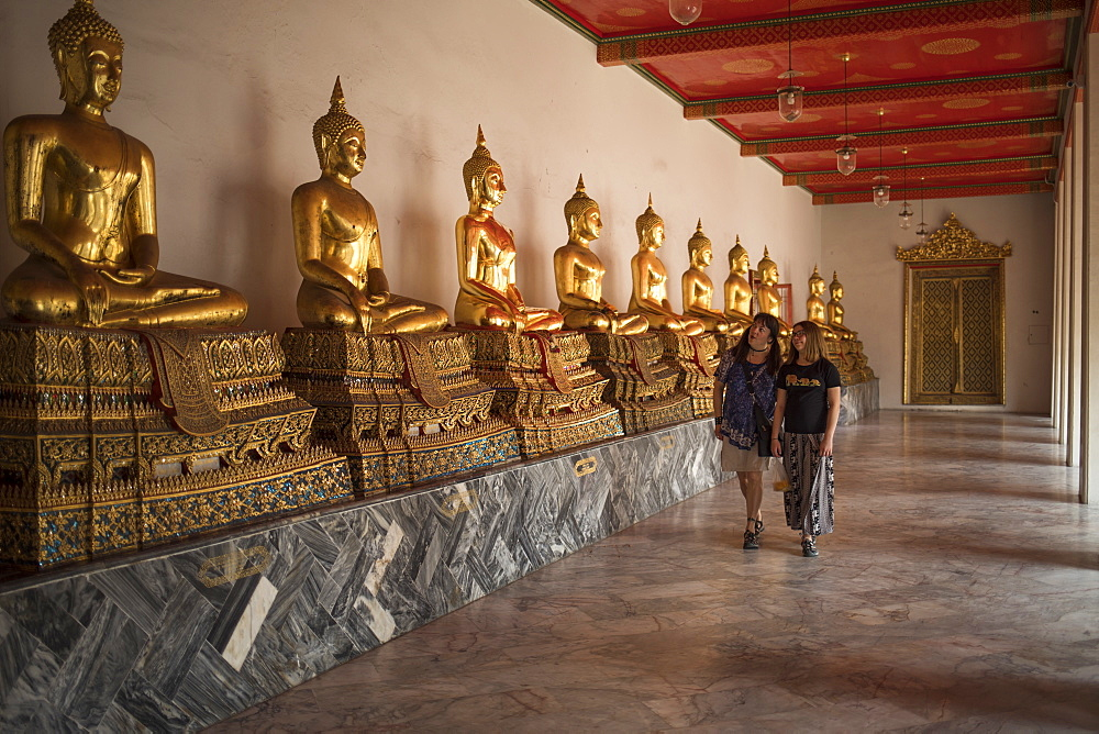 Front view of mother and daughter walking on Wat Pho, Bangkok, Thailand