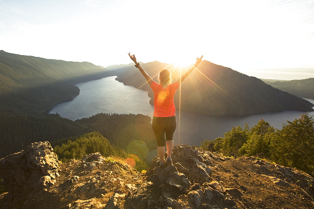 A female hiker in a red shirt celebrates reaching the top of the Mount Storm King trail in Olympic National Park at sunset.
