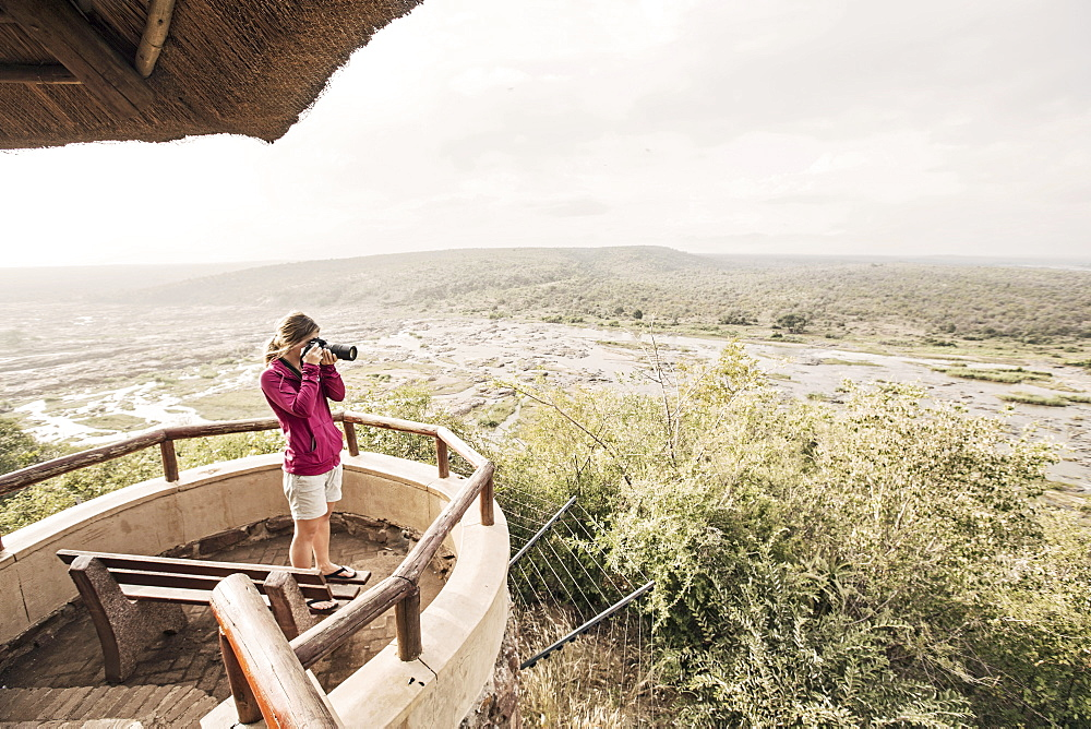 Female photographer taking picture at overlook in Kruger National Park, South Africa