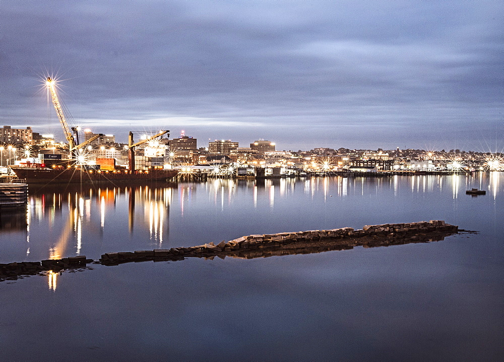 Portland, Maine's harbor is lit up in a long exposure at night.