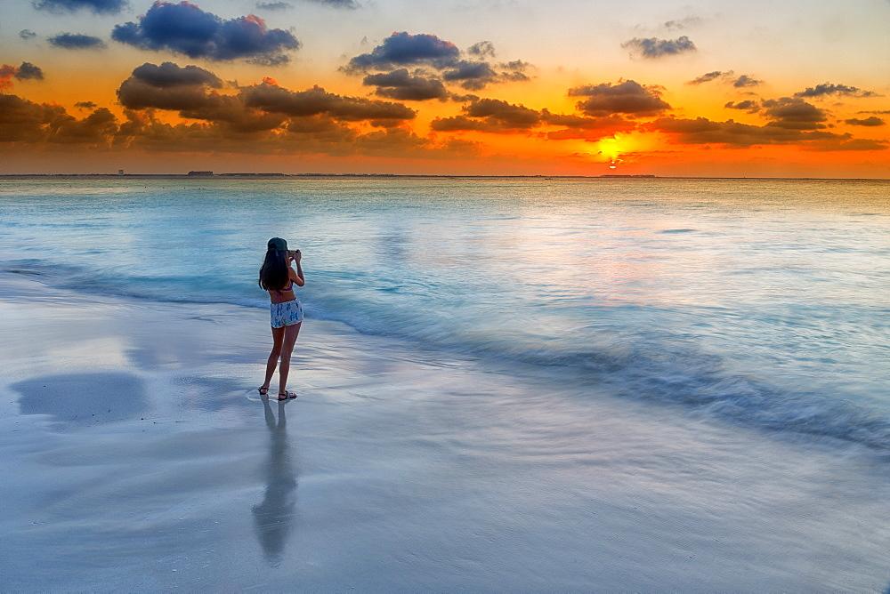 Photograph of woman photographing Caribbean Sea on beach at sunset, Isla Mujeres, Yucatan Peninsula, Mexico