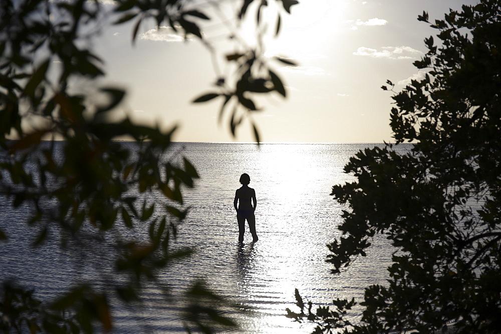 Silhouette of tourist sunbathing on idyllic beach in Holbox, Holbox Island, Cancun, Yucatan, Mexico