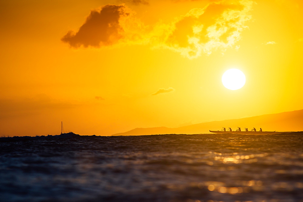 Group of men rowing in sea at sunset, Kaimana Beach, Honolulu, Hawaii, USA