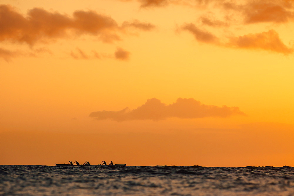 Group of men paddling in sea at sunset, Kaimana Beach, Honolulu, Hawaii, USA