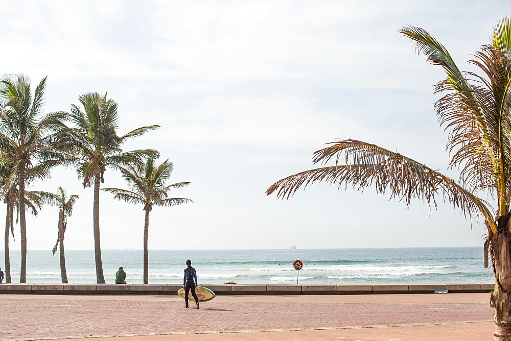 A boy with a surfboard walks down the promenade on the Golden Mile - named for its stretches of golden sand beaches - Durban, South Africa.