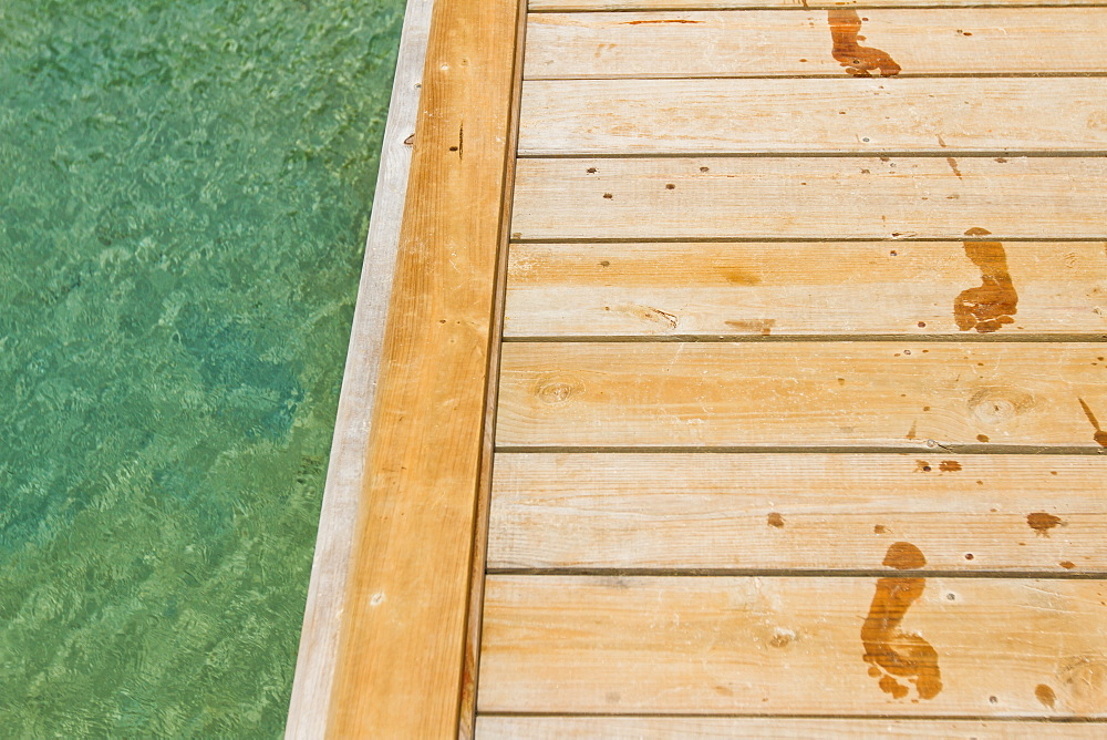 Wet footprints track on wooden pier next to sea, West End, Roatan, Honduras