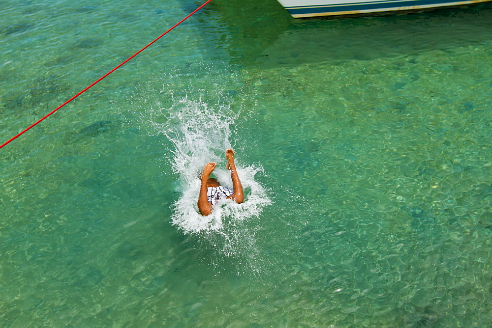 Boy jumps into water from wooden pier on West End, Roatan, Honduras