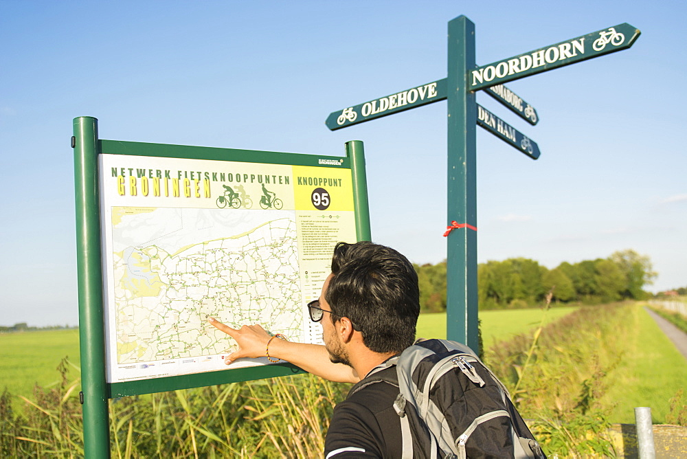 A young man wearing sunglasses, uses a map to find his way in the province of Groningen, The Netherlands, around the Netwerk Fietsknooppunten, a network of marked junctions of bycicle roads spanning all country Netherlands.